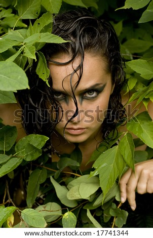 Sexy photo of a brunette posing with her head peaking out of a bunch of leaves
