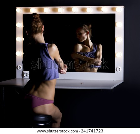 sexy slim girl in front of a mirror in the dark