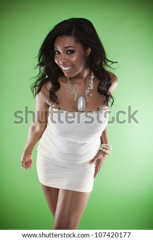 Sexy smiling African woman in a strapless cocktail dress leaning towards the camera provocatively flaunting her large breasts