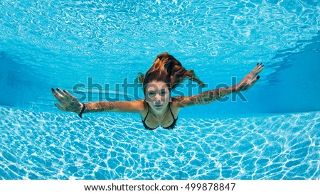 Sexy tattooed woman portrait wearing bikini underwater in swimming pool. Vacation, fun, lifestyle concept.