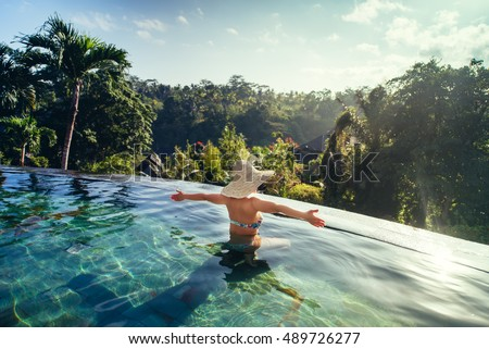 sexy woman enjoying the sun at infinity summer swimming pool at luxurious resort