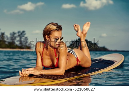 Sexy woman lying on a surfing board on the water in the sea