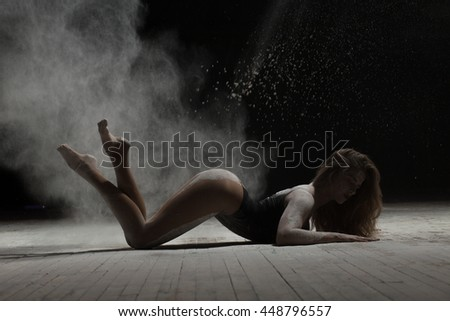 Sexy woman lying on floor and dancing with flour