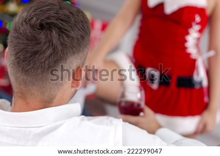 sexy woman santa  in red costume seduces man
