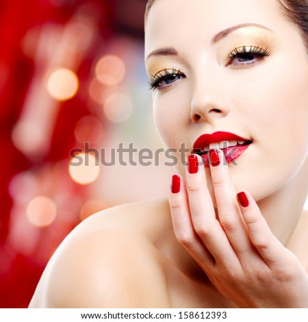 Sexy woman with golden makeup and red manicure
