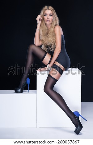 Sexy woman with long slim legs wearing stockings, looking at camera. Studio shot.