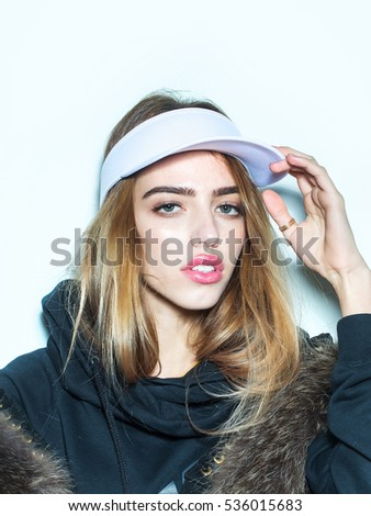 sexy young fashionable girl or woman with beautiful pink lips on pretty cute face with stylish long hair in sport cap and fur isolated on white background