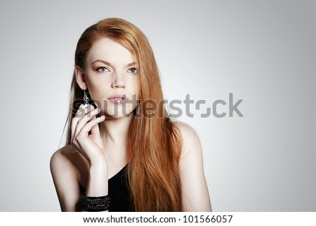 Sexy young red hair woman with jewellery on grey background