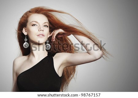 Sexy young woman with scatter red hair on grey background