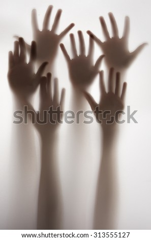 shadow of a hands behind transparent paper