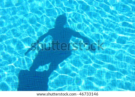 Shadow of young boy diving in the swimming pool