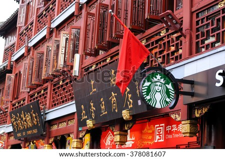 Shanghai, China - October 1, 2012: A Starbucks logo hanging on a classic Chinese building, under a Chinese national flag, along with other store signs, in a big shopping center - Yuyuan Tourist Mart.
