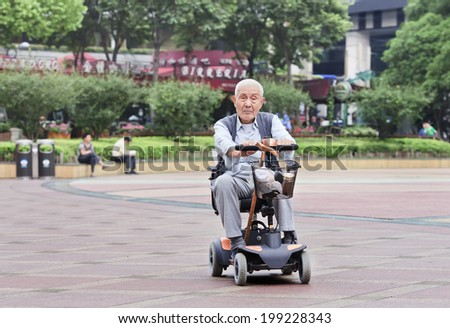 SHANGHAI-JUNE 4, 2014. Chinese elderly in an electric mini car. The population of the elderly (60 or older) in China is about 128 million or one in every ten people, which is the largest in the world.