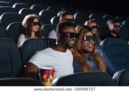 Sharing cinema romance. Beautiful young African woman enjoying a 3D movie at the cinema with her handsome boyfriend