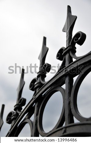 Sharp decorative iron fence against cloudy sky
