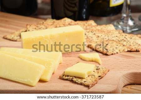 Sharp white cheddar cheese with crackers and wine, shallow DOF focus near front