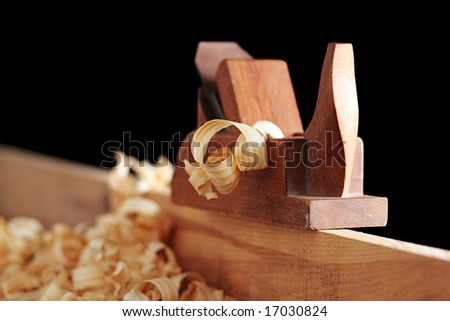 shaving and wooden plane on a black background