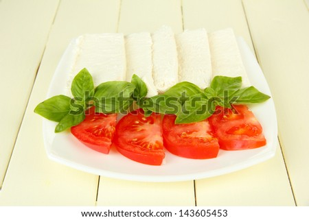 Sheep milk cheese, with basil and tomato on color wooden background