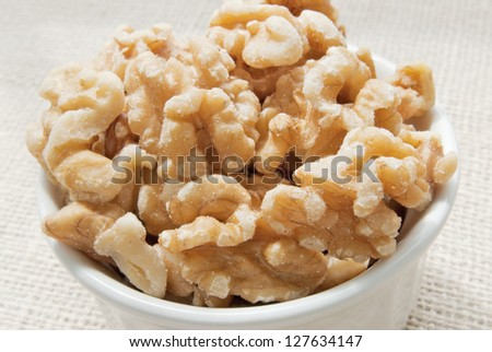 shelled walnuts in a white bowl with a burlap fabric background.