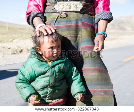 SHIGATSE, TIBET, CHINA - SEPTEMBER 18, 2015: Tibetan kid in a steppe in Tibet.