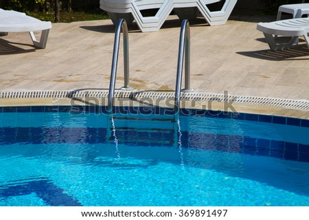 Shiny chrome ladder in the pool with blue water