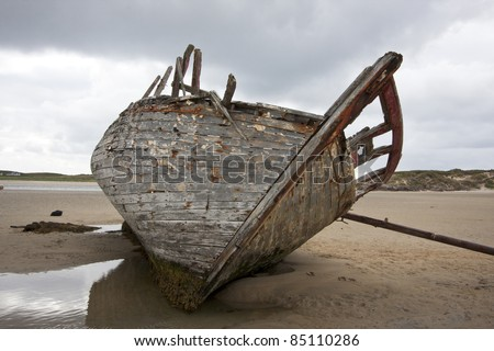 Shipwrecked boat lying on a sandy beach on the north coast of Ireland.