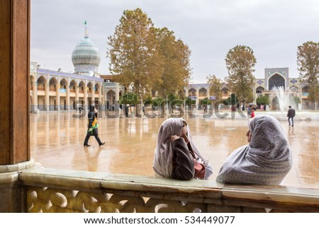 Shiraz, Iran - December 24, 2015: Two unidentified iranian woman talk to each other  in famous Shah-e-Cheragh Shrine and mausoleum (Mirror mosque) in Shiraz, Iran