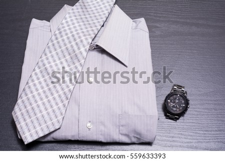 Shirt with tie and watch on black desk