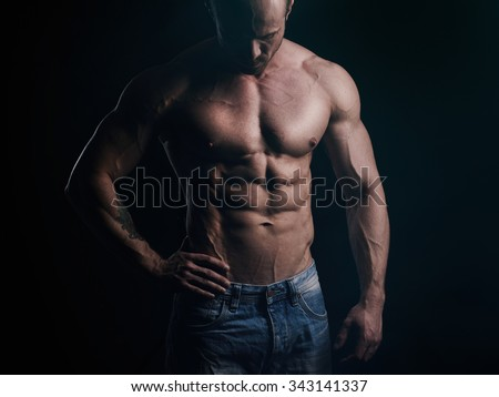 Shirtless athlete looking at his body
