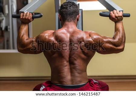 shirtless bodybuilder doing military press for shoulder