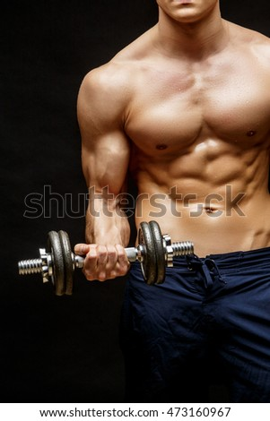 Shirtless bodybuilder holding dumbell and showing his muscular arms.