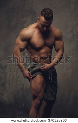Shirtless bodybuilder showing his muscular leg.