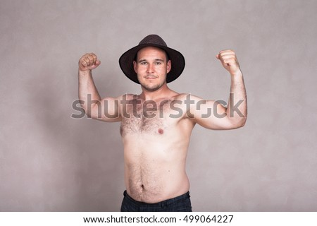 Shirtless man in hat posing and showing his strong arms and hairy body.