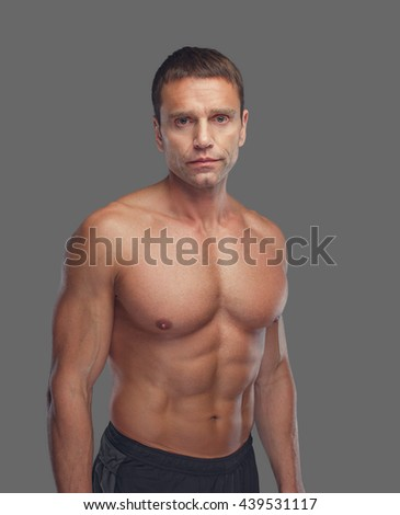 Shirtless muscular suntanned middle age male isolated on grey background.
