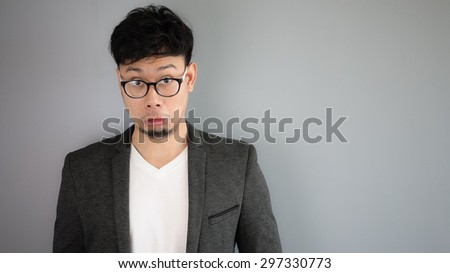 Shocked Asian businessman with glasses.