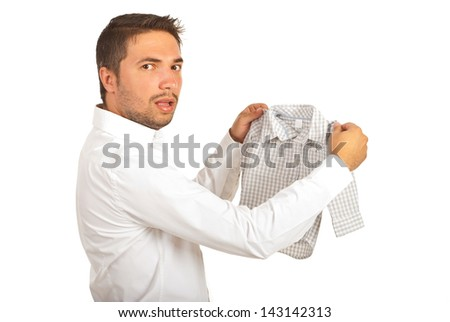 Shocked man holding shrunk shirt and looking at camera isolated on white background