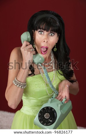 Shocked retro-styled woman holding telephone over maroon background