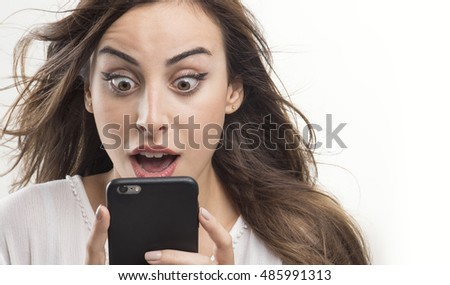 Shocked woman looking at phone, Young girl shocked looking at mobile
