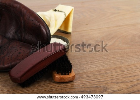 Shoes and cleaning equipment on a rustic wooden floor