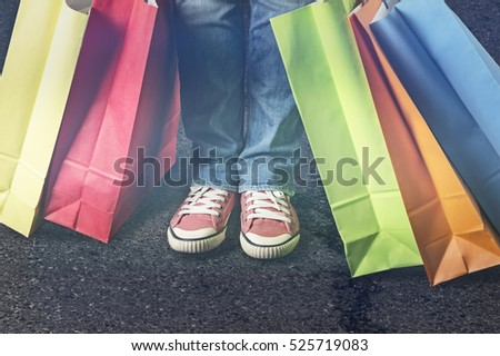 Shopping bags in various colors close to female feet