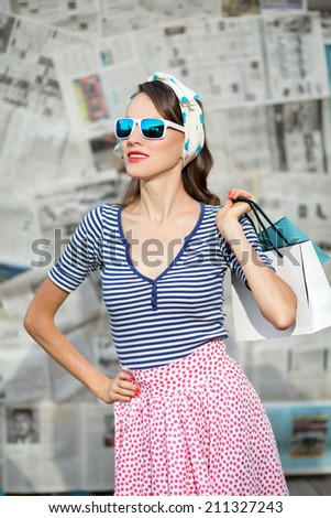 Shopping woman holding bags on gray grunge newspaper background. Summer shopping woman wearing sunglasses. Pinup. Emotions