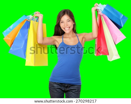 Shopping woman holding shopping bags above her head smiling happy during sale shopping spree. Beautiful young female shopper isolated on green background.