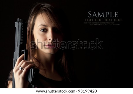 Shot of a beautiful girl holding gun, isolated on black bckground