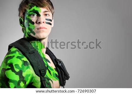 Shot of a conceptual soldier painted in khaki colors. Studio shot.