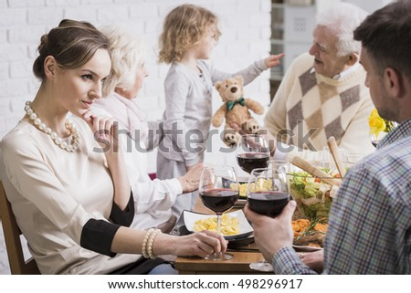 Shot of a family dinner with a young couple in the foreground