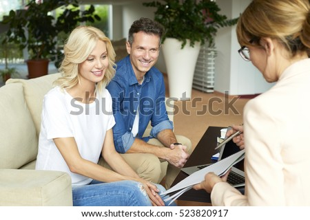 Shot of a happy middle aged couple consulting with real estate agent businesswoman in their home while sitting on couch.
