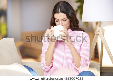 Shot of a happy young woman drinking tea at home while relaxing in living room.