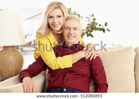 Shot of a loving wife embracing her husband from behind while at home in living room.