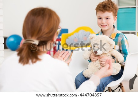 Shot of a smiling little boy sitting in a white chair and holding his teddy bear while talking to a child psychologist