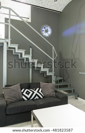 Shot of a sofa and a staircase in a modern grey apartment